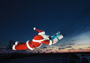 Santa Claus flying with wrapped gift
